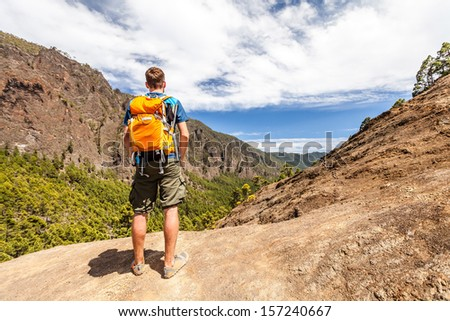 Hiking or trail running man in mountains. Backpacker looking at beautiful mountain view. Fitness and healthy lifestyle outdoors in summer nature, La Palma on Canary Islands. - stock photo