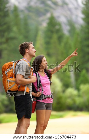 Hiking people. A couple of hikers pointing looking at nature in beautiful landscape mountains of Yosemite National Park, California, USA. Young multiracial couple on hike, Caucasian man, Asian woman. - stock photo