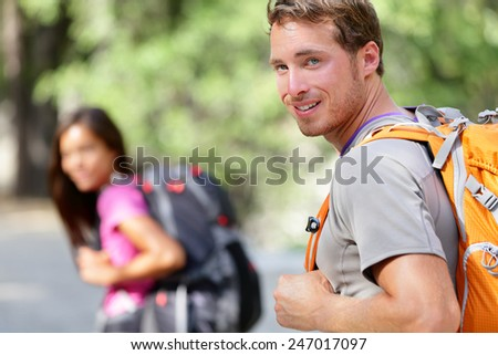 Hiking people. Young couple of hikers walking. Caucasian man smiling happy in foreground with young woman in background during summer trip in Yosemite National Park, California, USA. - stock photo