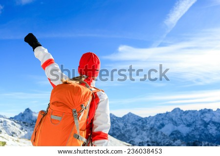 Hiking successful woman with arms outstretched, motivation inspiration in mountains. Fitness and healthy lifestyle outdoors in winter snowy beautiful nature - stock photo