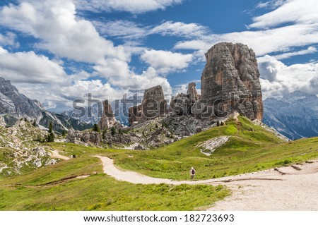 Hiking trail in the Cinque Torri Dolomites, against blue cloudy sky in the Summertime - stock photo