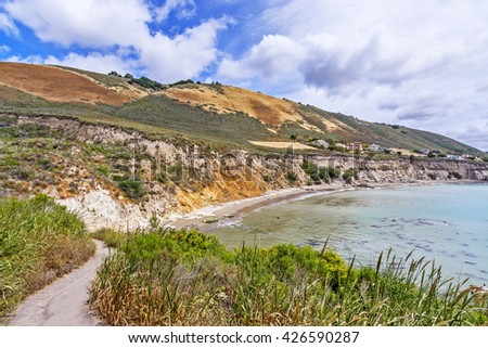Hiking trail / path towards Pirate's Cove, with aquamarine waters and puffy white clouds, perfect for resting, picnicking, hiking, biking, walking, & sunbathing. Photographed near Avila Beach. - stock photo