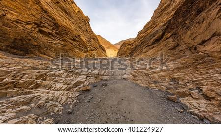 Hiking trail through the narrows at Mosaic Canyon. The canyon narrows dramatically to a deep slot cut. Mosaic Canyon, Death Valley National Park, California - stock photo