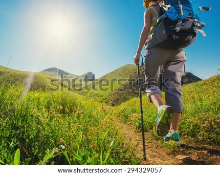 Hiking. Woman hikers walking on a grassy trail in the mountains. - stock photo