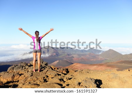 Hiking woman on top happy and celebrating success. Female hiker on top of the world cheering in winning gesture having reached summit of mountain, East Maui Volcano, Haleakala national park Hawaii. - stock photo
