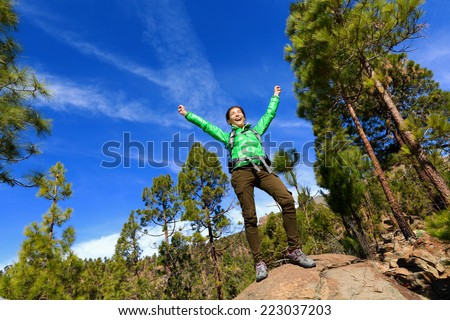 Hiking woman reaching summit top cheering celebrating on mountain top with arms up outstretched towards the sky. Happy female hiker. - stock photo