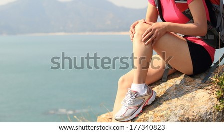 hiking woman sit seaside rock touch the injured knee - stock photo