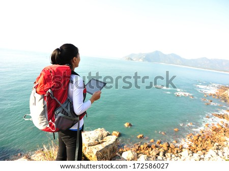 hiking woman stand on seaside rock and use digital tablet  - stock photo