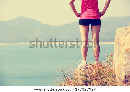 hiking woman stand seaside mountain rock looking at the view  - stock photo