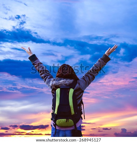 Hiking woman with her arms raised - stock photo