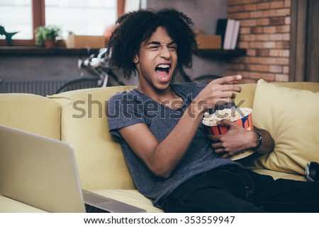 Hilarious TV show. Cheerful young African man watching TV and holding bucket of popcorn while gesturing on the couch at home - stock photo
