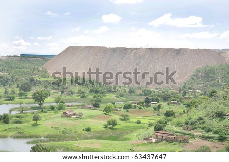 Hill formed by the overburden removed from coal mines near a village - stock photo