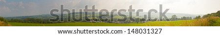 Hill landscape with meadow and trees and blue cloudy sky. Panoramic shot. Zuid Limburg. The Netherlands. - stock photo
