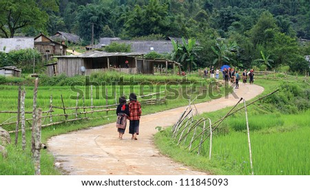 Hill tribe Red Dao children walk up to their village near terraced rice fields. Red Dao Minority are the 9th largest ethnic group in Vietnam. - stock photo