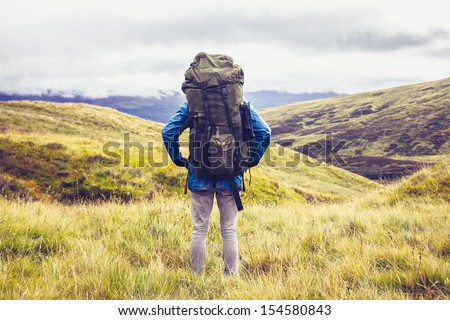 Hill walker standing in the middle of mountain wilderness - stock photo