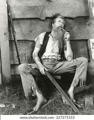 Hillbilly smokes clay pipe - stock photo