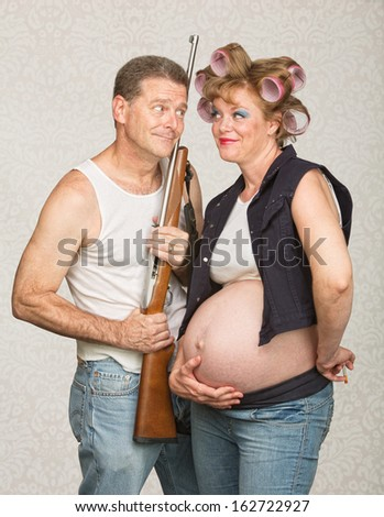 Hillbilly with rifle and adoring pregnant wife - stock photo
