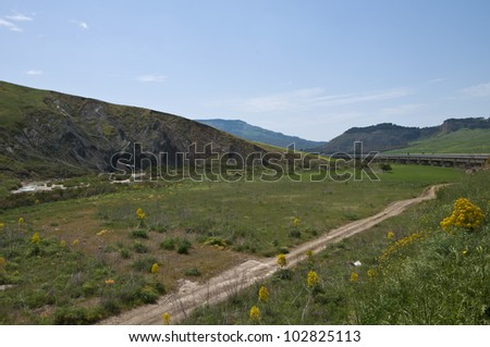 Hills and green valleys of Sicily with a road. - stock photo