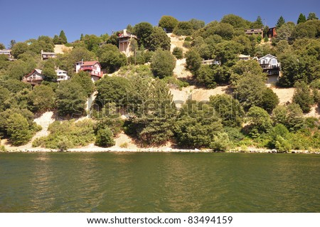 Hillside homes sit above the shoreline of scenic Lake Gregory in the Southern California mountains. - stock photo