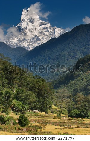 Himalayan countryside with Machhapuchhre mountain in background - stock photo