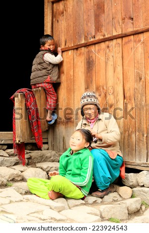 HIMALAYAS, NEPAL, MARCH 22: Nepali woman with her children near the house. Woman with braids daughter. Everest region, Himalayas, in Nepal on March 22, 2014   - stock photo