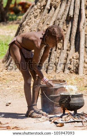 Himba Boy cooks for Lunch - stock photo