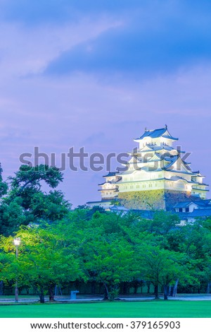 Himeji-jo castle lighted at evening sunset with deep purple sky and foreground trees from nearby park in Himeji, Japan after 2015 completely renovated. Vertical copy space - stock photo