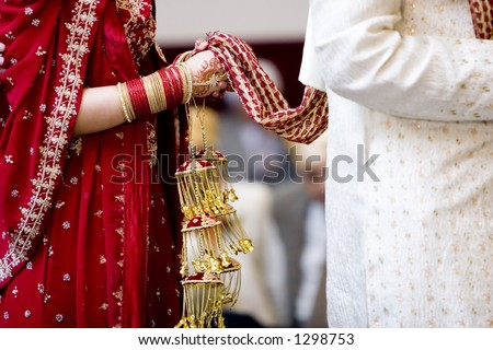 hindu bride walks behind husband holding garb - stock photo