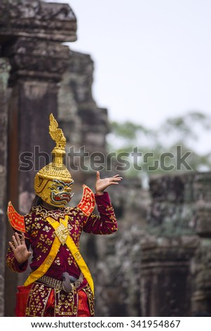 Hindu cultural legend of deity with hands gestures reenacting by an actor in colorful costume at Bayon temple ruins, Angkor Wat, Siem Reap - stock photo