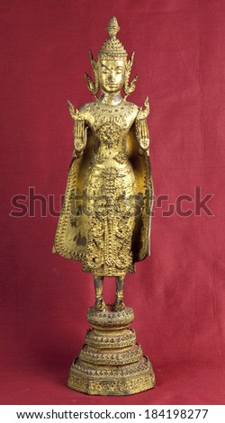 Hindu deity statuette on oxblood red background - stock photo