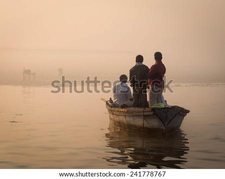 Hindu pilgrims approaching the East bank of the Ganges river by boat in Varanasi, Uttar Pradesh, India. - stock photo
