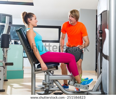 Hip abduction woman exercise at gym indoor closing legs and personal trainer blond man - stock photo