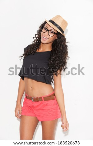 Hip and stylish. Attractive young African woman in glasses and funky wear looking at camera and smiling while standing against white background - stock photo