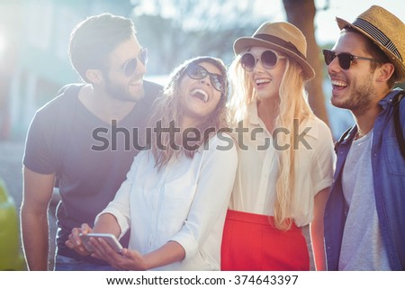 Hip friends checking at smartphone on the streets - stock photo