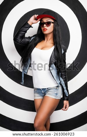 Hip hop girl. Attractive young African woman adjusting her cap while posing against black and white background - stock photo