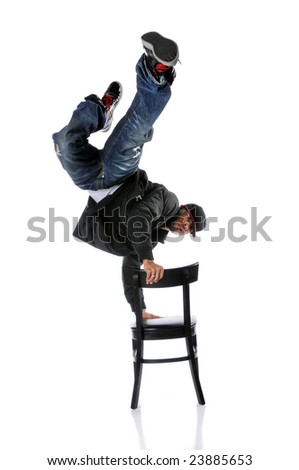 Hip hop man performing dance standing on chair - stock photo