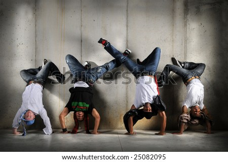 Hip Hop men performing dance with handstand over grunge background - stock photo