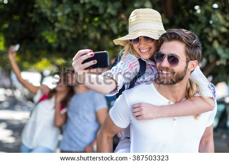 Hip man giving piggy back to his girlfriend and taking selfie on the street - stock photo