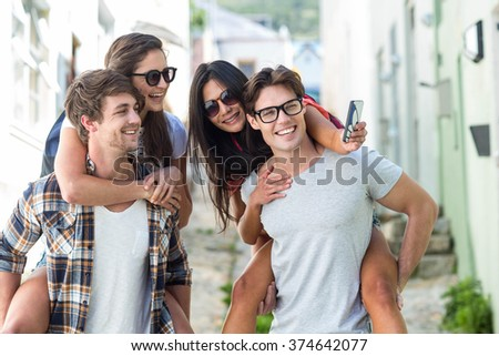 Hip men giving piggy back to their girlfriends and taking selfie on the street - stock photo