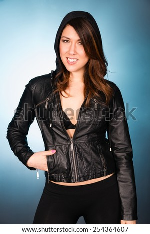 Hip Smiling Young Adult Woman Wearing Leather Jacket Hooded Sweatshirt - stock photo