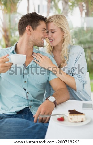 Hip young couple enjoying coffee and desert together on the cafe terrace on sunny day - stock photo