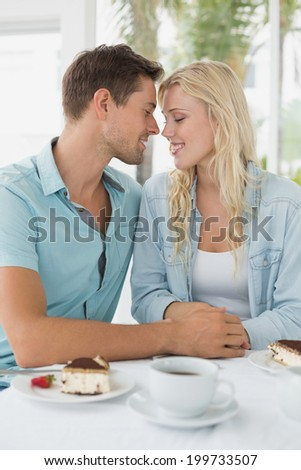 Hip young couple having desert and coffee together on the cafe terrace on sunny day - stock photo