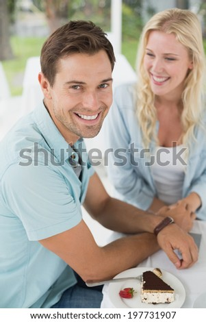 Hip young couple having desert together on the cafe terrace on sunny day - stock photo