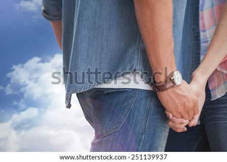 Hip young couple holding hands against mountain peak through the clouds - stock photo