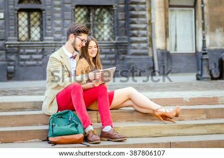 Hip young couple looking at tablet together, outdoor, city - stock photo