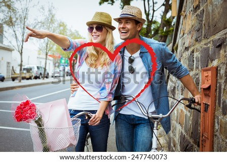 Hip young couple standing by brick wall with their bikes against heart - stock photo