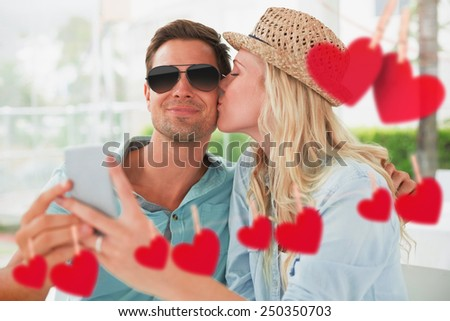 Hip young couple taking a selfie together against hearts hanging on a line - stock photo