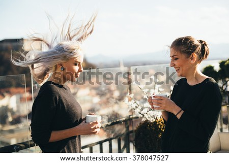 Hip young women talking in roof top cafe on windy day - stock photo