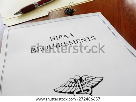 HIPAA healthcare requirements document with folder and pen                                - stock photo