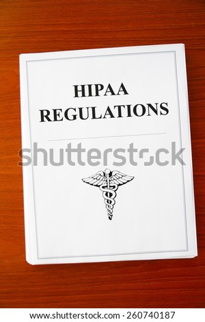 HIPAA Regulations documents on a desk - stock photo